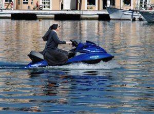 In Venice, a nun rides a jet-ski.